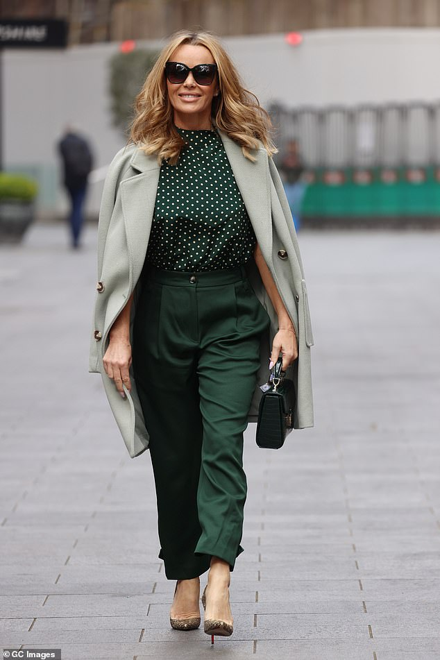 Green with envy: The presenter, 50, cut a chic figure in a silk green polka dot top and emerald suit trousers