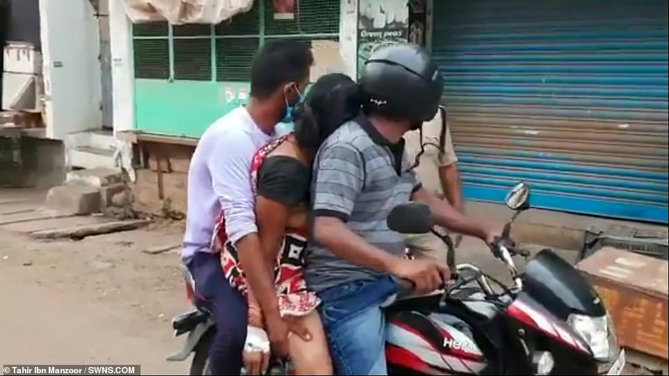 With no ambulances available to take her for cremation, the brothers were forced to pin her dead body between their own and ride on a motorbike for nine miles so she could be given her last rites