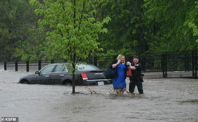 A police officer is seen helping a woman from her car during flooding in northwest Arkansas on Wednesday