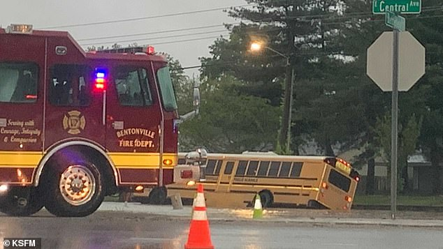 First responders are seen preparing to assist a driver after a bus was overcome with flood waters in Arkansas