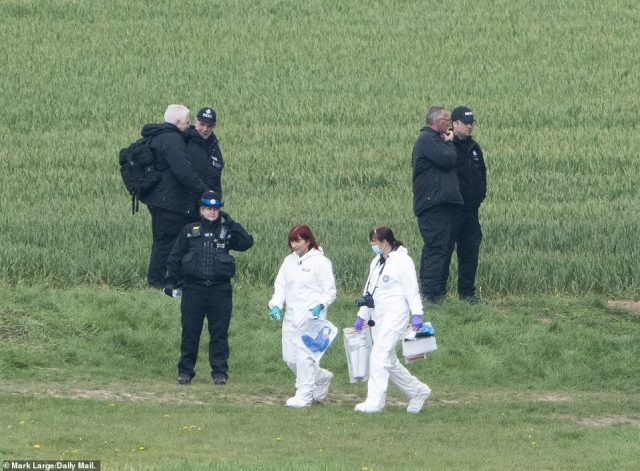 These forensics officer were seen taking away items from the scene including what appears to be a blue bag or an item of clothing