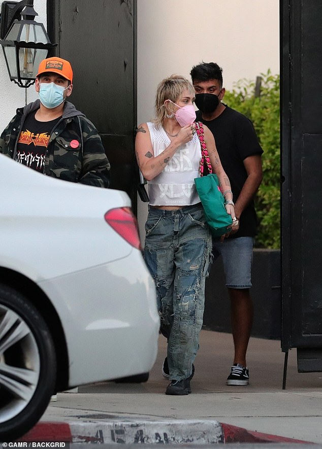 Company:  Miley, 28, was dressed in a white Gautier tank and very distressed jeans. She carried a green tote over one shoulder and was accompanied by a couple of male pals