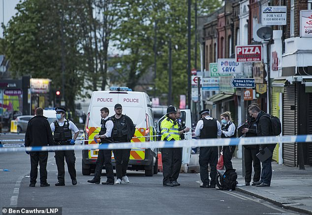 The son - who has not been named - desperately tried to intervene as his father was repeatedly stabbed before an ambulance arrived. Pictured: Police officers at the scene on Thursday