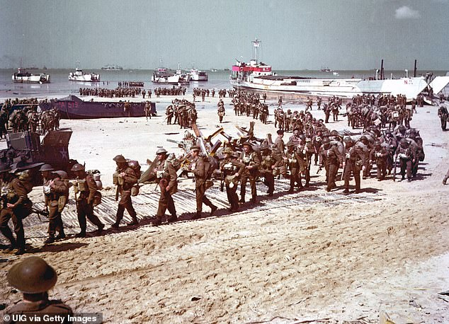 After the initial assault: British soldiers make their way up Juno Beach