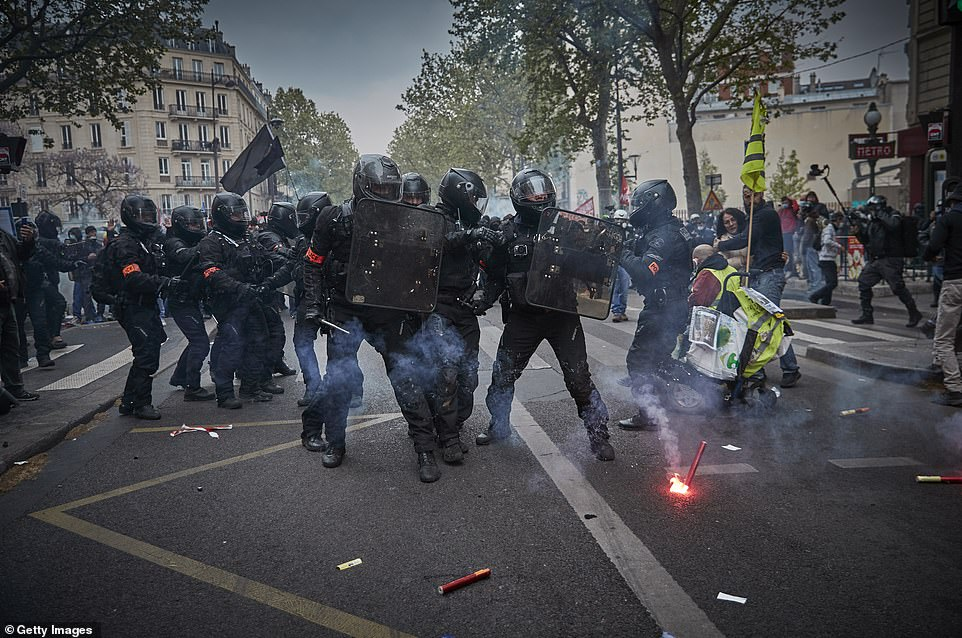 PARIS, FRANCE: Riot police with shields move in to quell the disruption as red hot flares are hurled in their direction near thePlace de la Republique