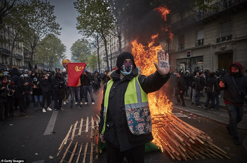 PARIS, FRANCE:A Gilet Jaune, or yellow vest, protestor stands in front of a burning barricade holding his hand up with an inscription calling for President Macron to resign