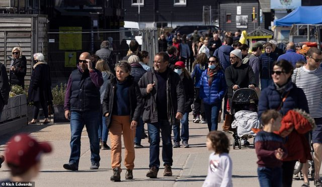 Huge numbers of people donned coats and hats to fight off the chill today as they made their way to the beach in Whitstable, Kent, to enjoy the sunshine