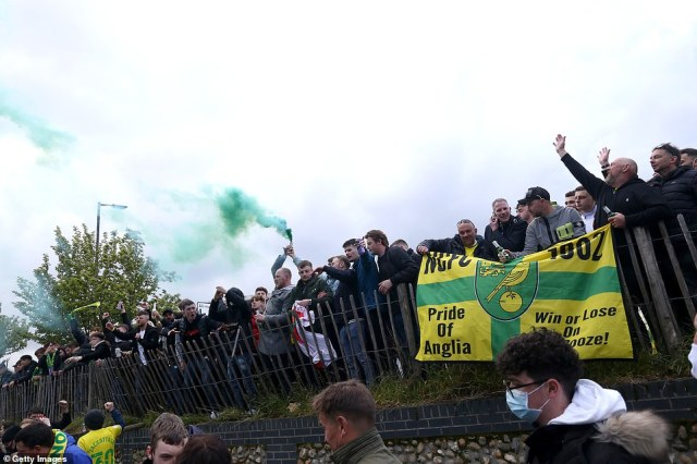 Green smoke is let off by one fan outside the grounds of Norwich City FC earlier today as many fans gathered to celebrate their side's title win