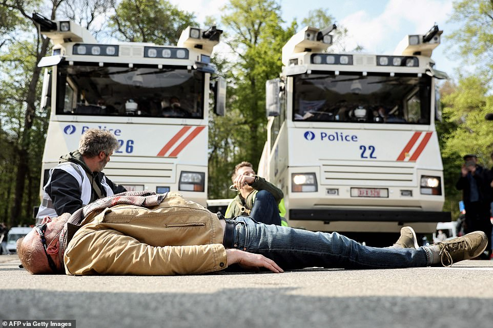 BRUSSELS, BELGIUM: A man lies down in front of police vehicles equipped with water cannons in Brussels earlier today