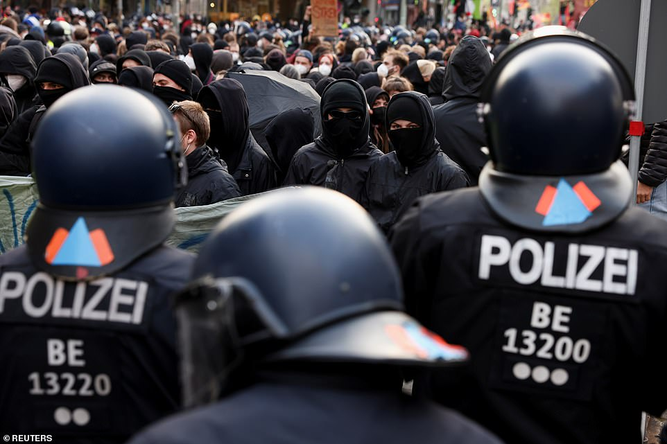BERLIN, GERMANY: A row of police officers in Berlin stand in front of a large group of protestors earlier today