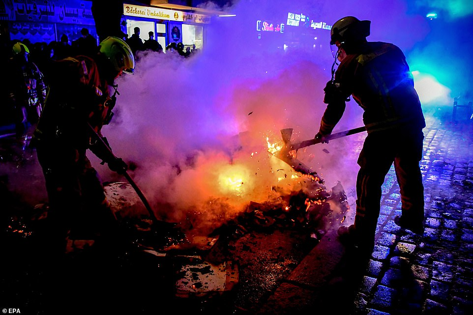 BERLIN, GERMANY: Firefighters work to extinguish a blaze on a street during a May Day protest in Berlin this evening