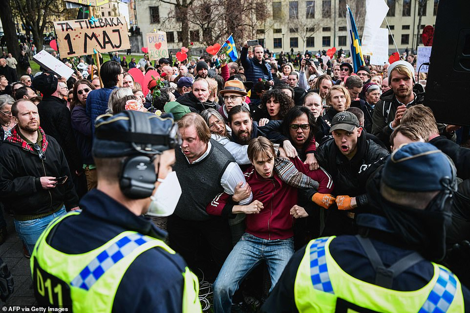 STOCKHOLM, SWEDEN: Demonstrators on the streets of the Swedish capital lock their arms together in a line to prevent police officers from breaking up the crowd earlier today