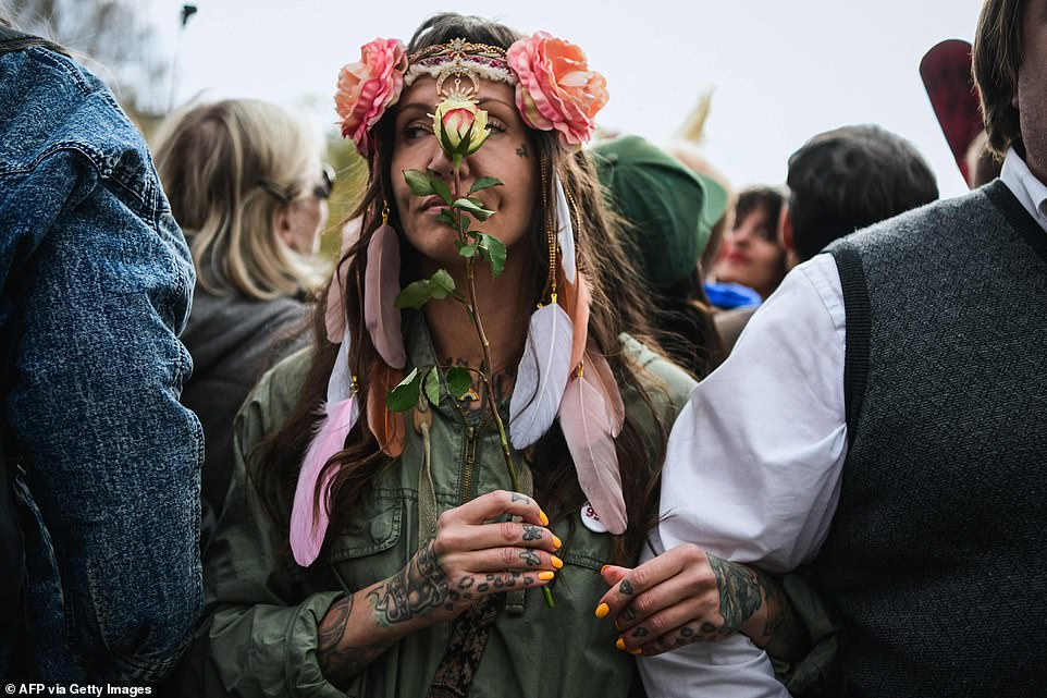 STOCKHOLM, SWEDEN: A tattooed woman holds a white rose in her hand earlier today as she joined hundreds of people taking to the streets to protest against coronavirus restrictions