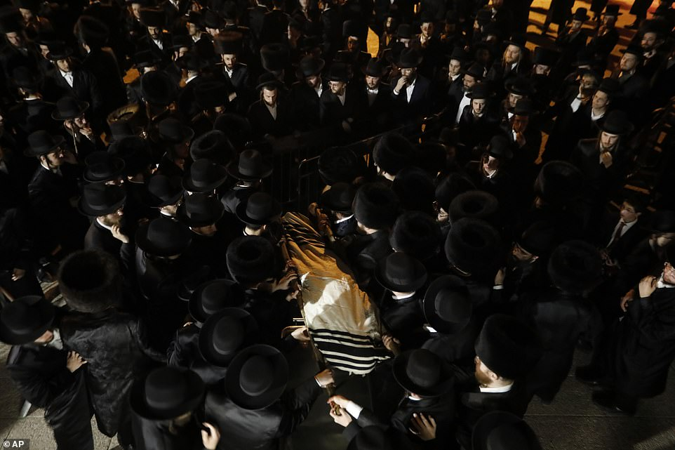 Mourners carry the body of Mr Knoblovitz.A stampede at a religious festival attended by tens of thousands of Ultra-Orthodox Jews in northern Israel killed dozens of people and injured about 150