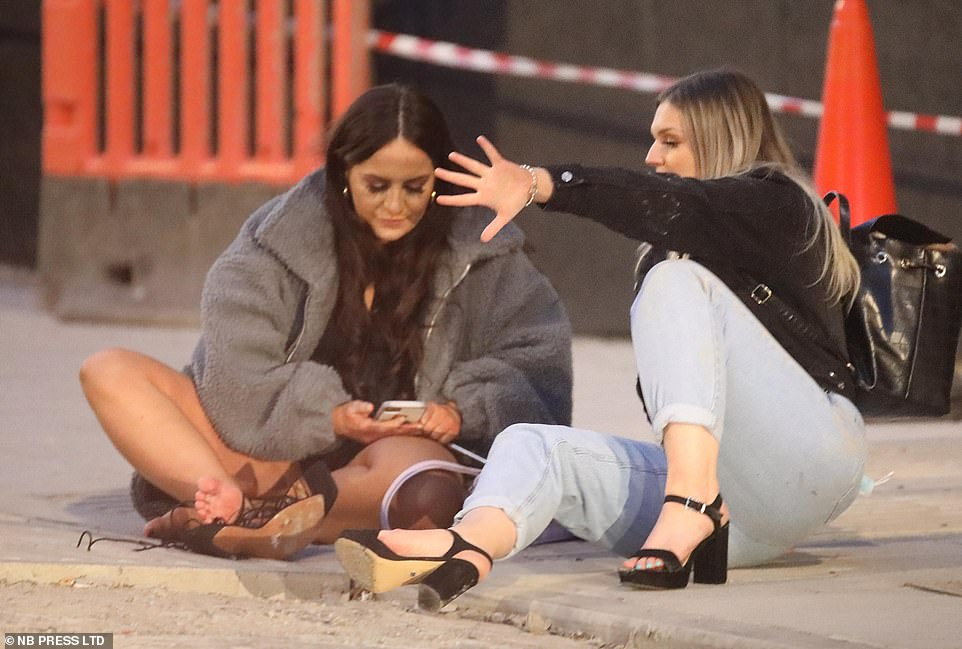 Two women sit down on the pavement in Leeds on Saturday night as people headed out to make the most of their weekend