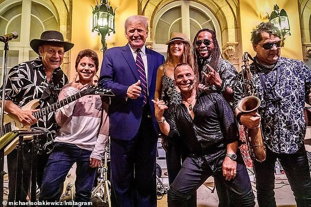 Former President Donald Trump poses with a group of fans at Mar-A-Lago on Thursday