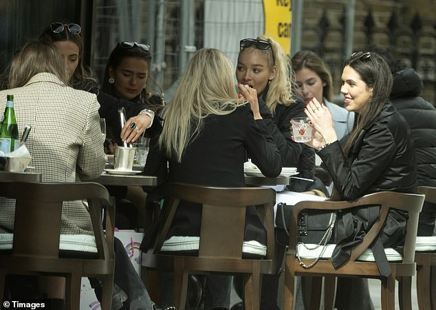Catch up: The model appears to be in good spirits as she enjoys time with her friends in London