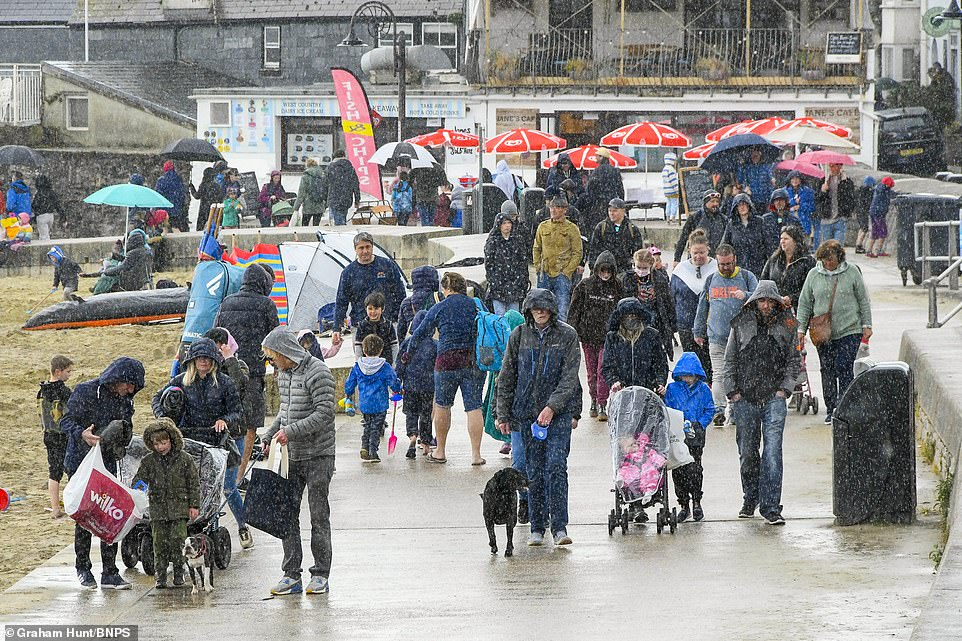 Families and visitors wearing waterproof jackets and carrying umbrellas brave the rain and flock to the at the seaside resort of Lyme Regis in Dorset