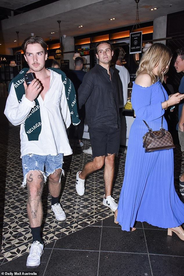 Stylish: He opted for an all black ensemble which consisted of a long sleeve button-up shirt, and ripped denim shorts