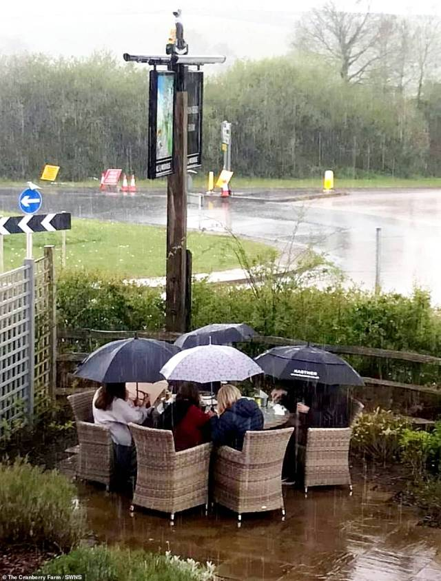 A group of hardy pub goers enjoy an outdoor pint in the pouring rain outside The Cranberry Farm pub, in Exeter, Devon