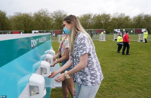 Revellers use hand sanitisers as they arrive for the music festival in Sefton Park in Liverpool