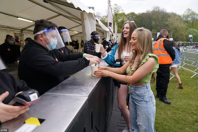 Bar staff wear masks and face visors as they serve revellers at the music festival in Liverpool today