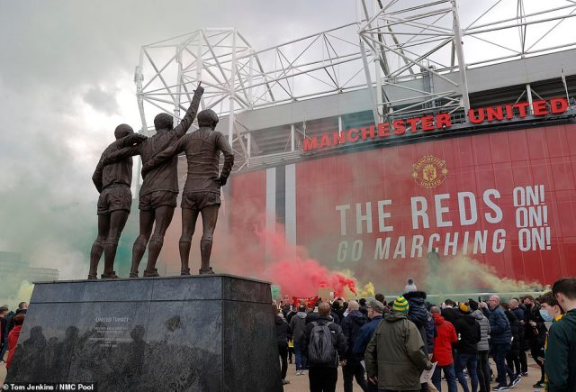 Fans light coloured smoke flares in front of the 'United Trinity' statue of George Best, Denis Law and Bobby Charlton