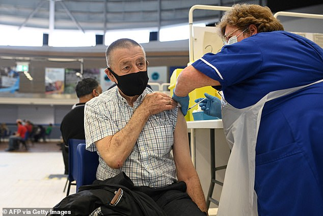 With the UK set to exceed 50million vaccinations today, ministers and health officials hailed the 'incredibly important' step towards Britain's return to normality (pictured: stock image of man receiving the Pfizer vaccine in Derby)