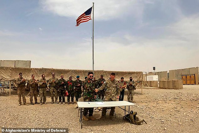 A US soldier and an Afghan National Army soldier shaking hands during a handover ceremony at Camp Antonik in the Helmand province on Saturday