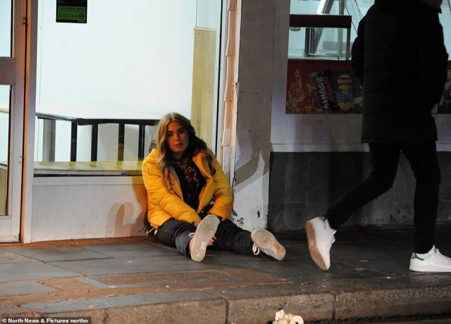 A reveller sits on the pavement as crowds are seen arriving to Newcastle City Centre to enjoy a night out on Sunday