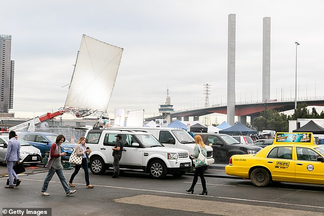 A general view of the filming set as extras are seen walking across the La Brea set at Docklands Studios