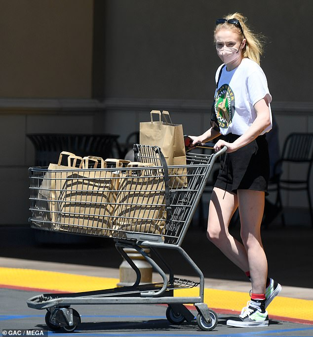 Casually cool: The Game Of Thrones star, 25, showcased her long, lean legs in a pair of black high-waisted shorts, which she teamed with a white Sophie Miller graphic T-shirt