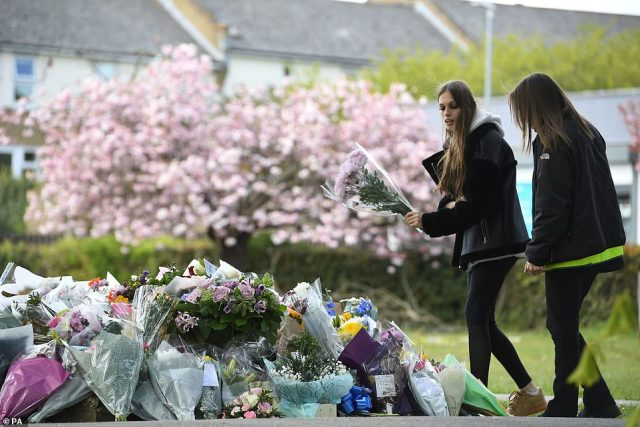 Two women lay flowers in a park in Aylesham village yesterday close to the scene where PCSO Julia James was found