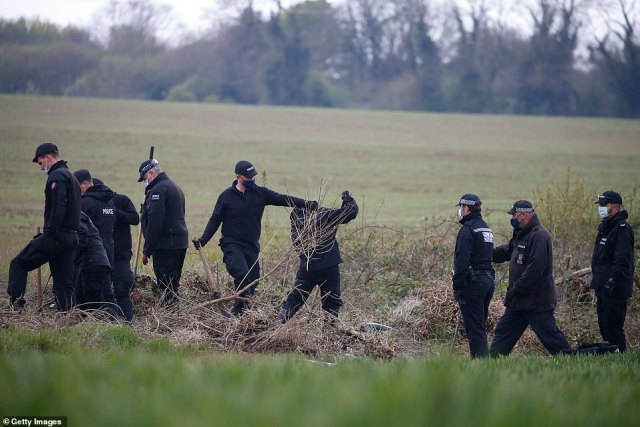 Police officers conduct a search in a field not far from Ackholt Wood on Sunday