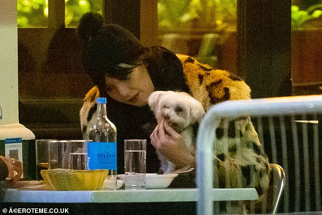 Eating leftovers: As the evening turned chillier, the pair, who were sat in the outdoor dining area of the restaurant, put on woolly hats - Daisy opting for a black bobble hat as she fed Monty