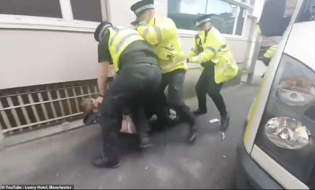 Several officers can be seen dragging one protester away before pinning him to the ground