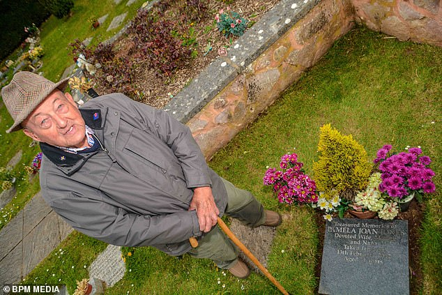 Neighbours were shocked when they saw Bill Jones (pictured by his wife Pam's gravestone), 85, from Tiverton, outside his garage after recently being told that he had died