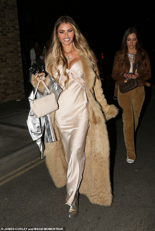 Glam: Chloe rocked a floor-length champagne satin dress under a long cream fur coat for the night out and put her own stamp on the look with some metallic cowboy boots