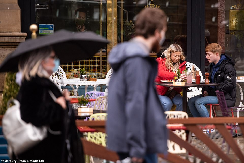People are spotted with raincoats and umbrellas making the most of Bank Holiday Monday in Manchester