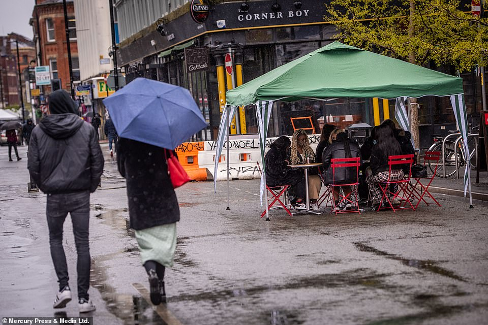 Diners battle through the rain as they sit outside to enjoy a meal in Manchester today