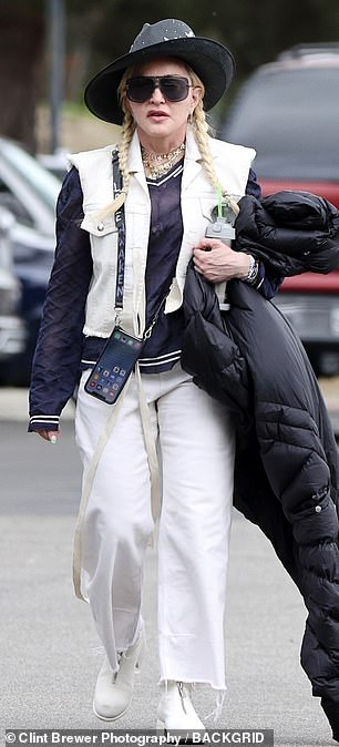 Monochrome madness: She sported a long black down jacket over a white denim jacket and black shirt