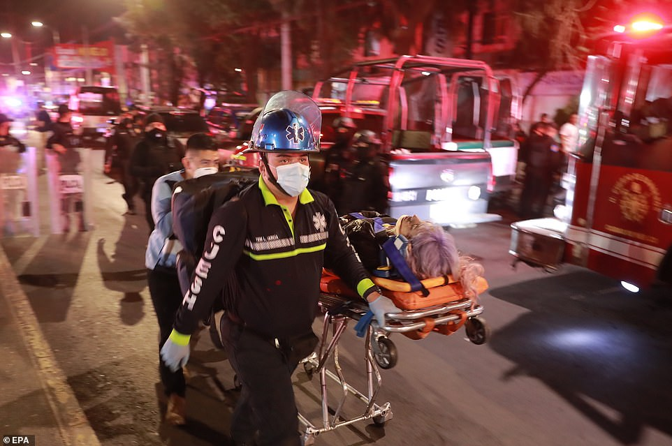 A fireman takes a person on a stretcher and wearing a neck brace into a waiting ambulance in Mexico City