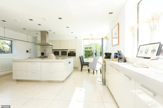 Cooking:The modern white kitchen features built-in, industrial-grade appliances and a square island, as well as a table to eat by the almost floor length windows