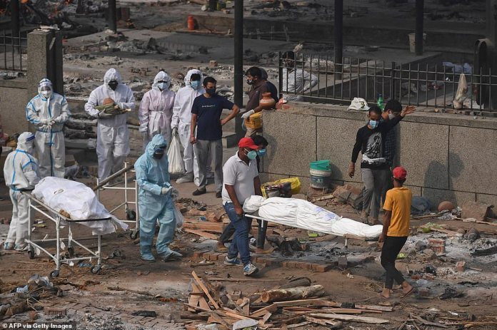 Los hospitales, morgues y crematorios se han visto desbordados, ya que el país ha informado de más de 300.000 casos diarios durante más de 10 días seguidos.  En la imagen: los cuerpos de las víctimas que murieron de Covid-19 se transportan en camillas antes de ser incinerados en Nueva Delhi el 2 de mayo.