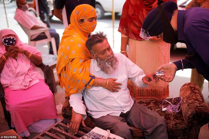 Un voluntario utiliza un oxímetro de pulso para comprobar la saturación de oxígeno de la sangre de un hombre antes de proporcionarle oxígeno en un Sikh Gurudwara en Ghaziabad, India.