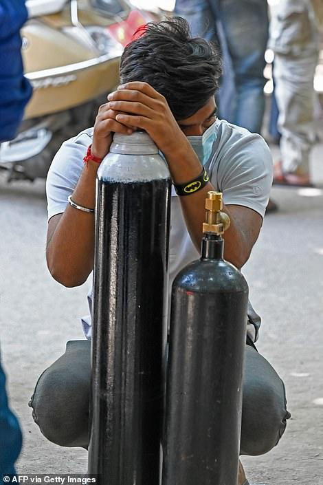 Un hombre espera para recargar su cilindro de oxígeno médico para el paciente con coronavirus Covid-19 en cuarentena domiciliaria en un centro de recarga privado en Delhi.