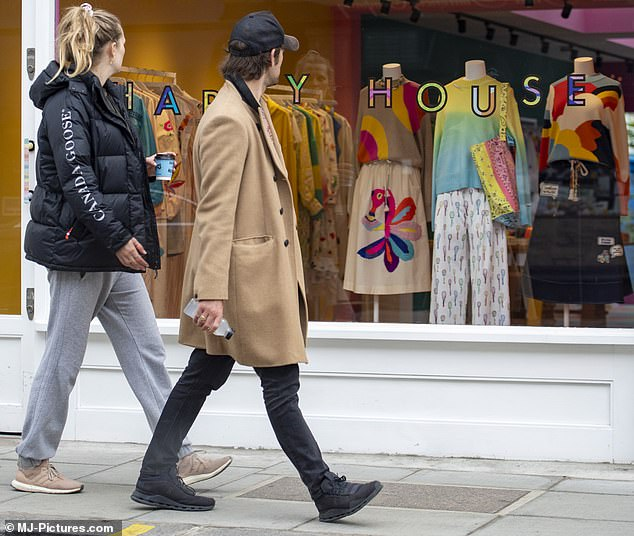 Pop of color: The couple looked at the colorful outfits in a shop window in West London