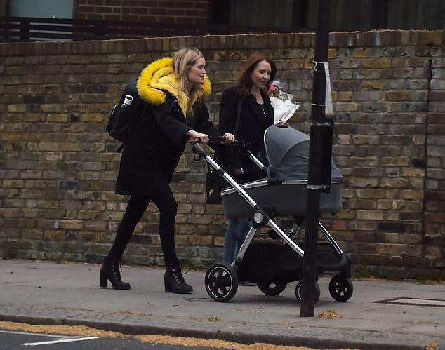 Doting mum: The Celebrity Juice star, 35, flashed a broad smile as she looked down at her bundle of joy while strolling down the street with her pal