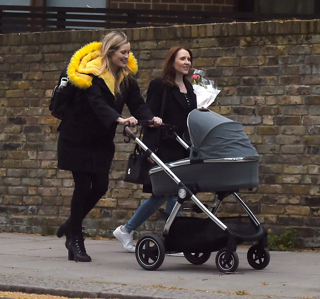 My girl:Laura Whitmore looked every inch the doting mum as she pushed her little girl in her pram while enjoying a Bank Holiday outing in London's Primrose Hill with Iain Stirling and their pals on Monday