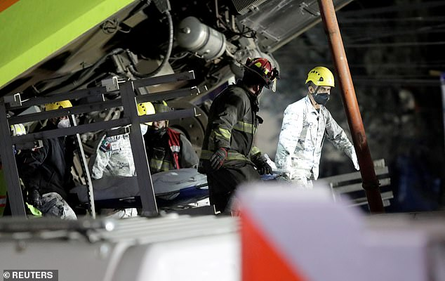 Rescue workers carry a body out from underneath a train that collapsed on to a highway in Mexico City, killing 24 people